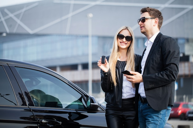 La visite réussie chez le concessionnaire. heureux jeune couple choisit et achète une nouvelle voiture pour la famille