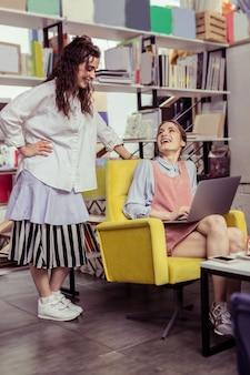 Visiter un café élégant. fille aux cheveux longs en tenue surdimensionnée debout au-dessus de son amie maigre pendant qu'elle travaille avec un ordinateur portable