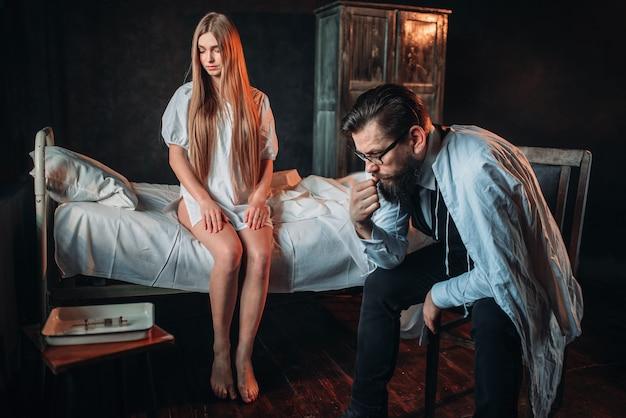 Visiteur assis contre une femme malade dans son lit d'hôpital