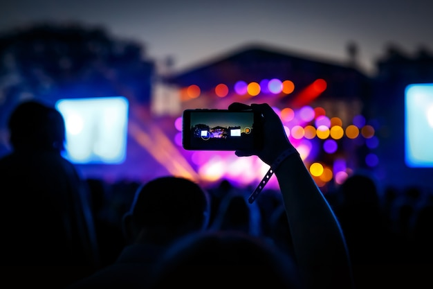 Un visiteur du concert filme une vidéo sur un smartphone.
