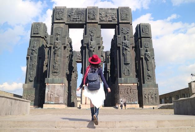 Visiteur féminin impressionné par la chronique de géorgie, un gigantesque 16 piliers env. monument de 30 mètres de haut, tbilissi, géorgie