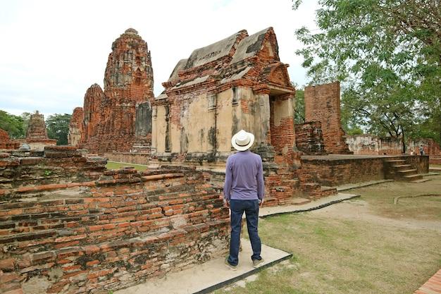 Visiteur impressionné par wat mahathat temple médiéval dans le parc historique d'ayutthaya, thaïlande