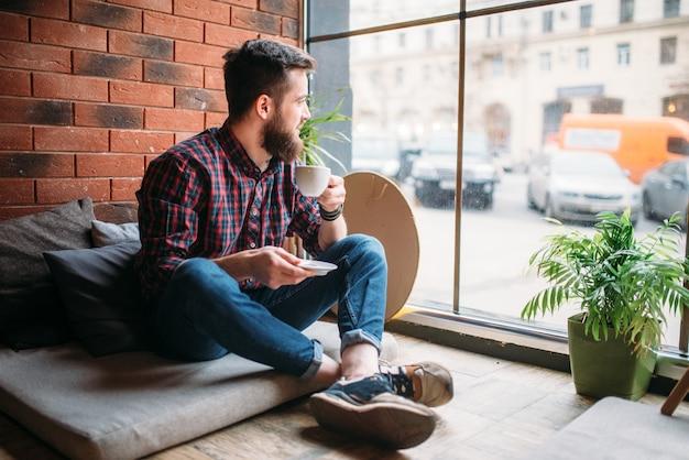 Un visiteur masculin assis dans un café en boisson boisson. loisirs de sexe masculin dans un pub