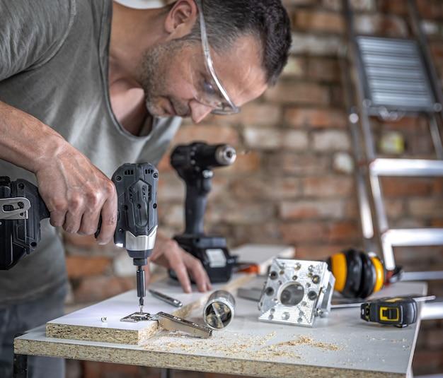 Vissage d'une vis autotaraudeuse dans un trou de fixation métallique sur une lame de bois à l'aide d'un tournevis, travail d'un menuisier.