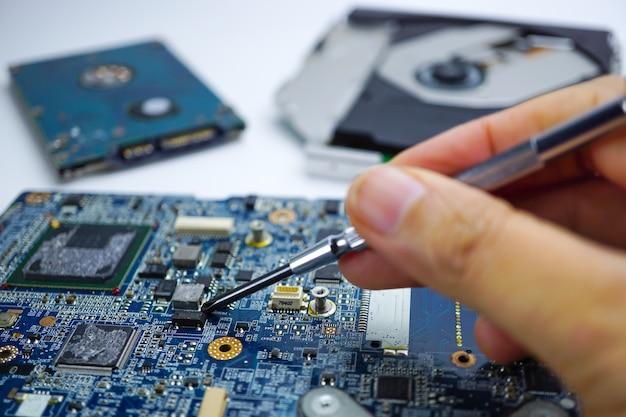 Visser le matériel informatique de la carte mère de l'ordinateur. technologie de maintenance de réparation.