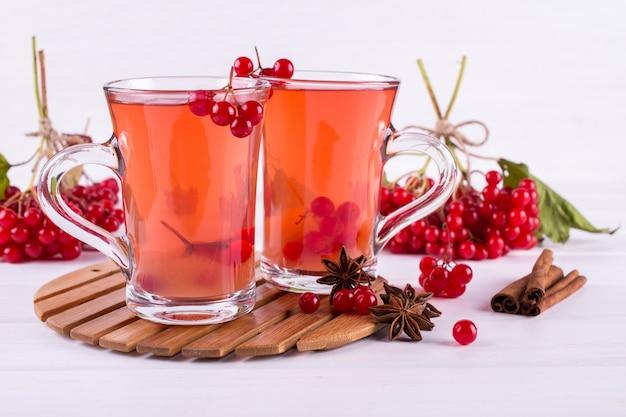Vitamine saine baie de viorne boisson chaude dans des tasses en verre avec des baies de viorne crues fraîches et des bâtons de cannelle, des étoiles d'anis sur une table de cuisine blanche.