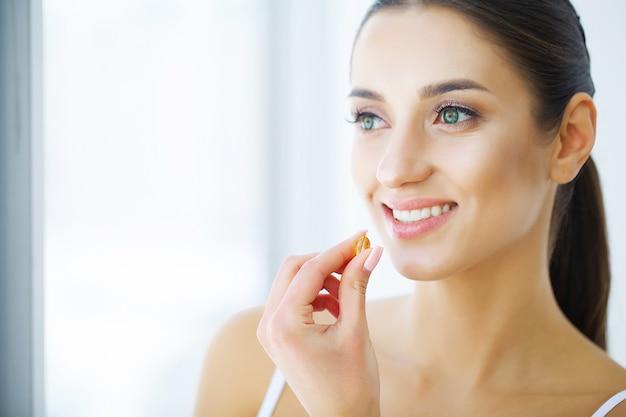 Vitamines. alimentation saine. happy girl avec capsule d'huile de poisson oméga-3. concept de régime sain.