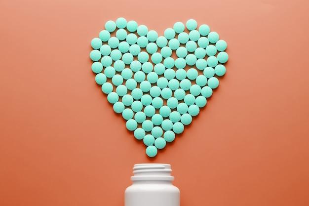 Vitamines b 12 sur un substrat rouge en forme de cœur, coulées dans un bocal blanc.