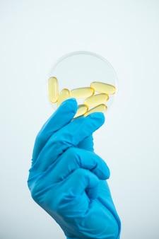Vitamines.close up of girl tenant la pilule avec de l'huile de foie de morue oméga-3. nutrition. suppléments nutritifs sains. sport, concept de régime. vitamine d, e, une huile de poisson en capsules et suppléments diététiques