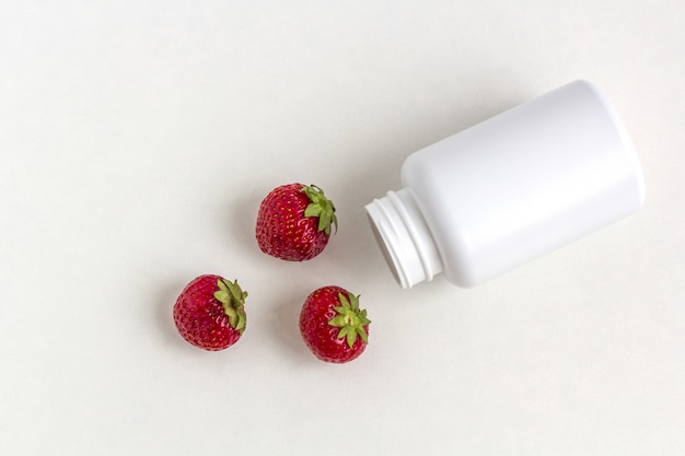 Vitamines fraîches sous forme de fraises de flacon de pilules blanches médecine.