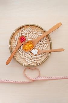Vitamines, minéraux et suppléments nutritionnels dans des cuillères en bois à l'intérieur d'une assiette en bambou tressé
