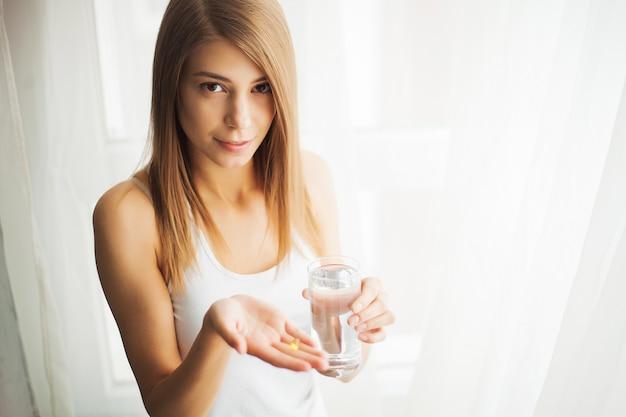 Vitamines et suppléments. femme prenant une tablette. fermez la main avec une pilule et la bouche.