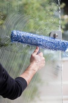 Vitre savonneuse avec raclette nettoyant la vitre