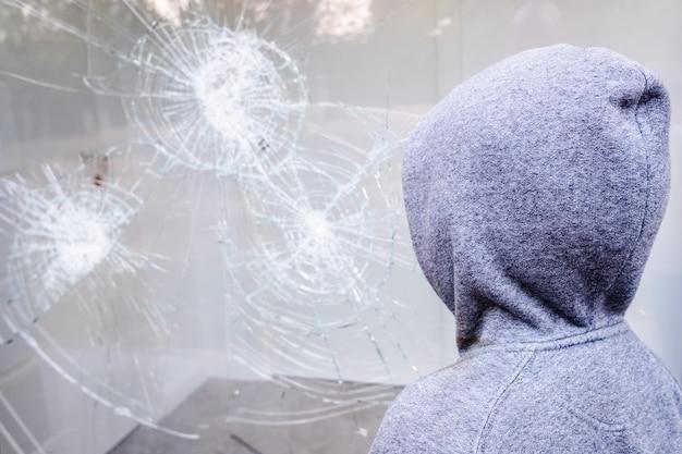 Vitrine avec verre brisé lors d'une manifestation dans une ville avec des manifestants.