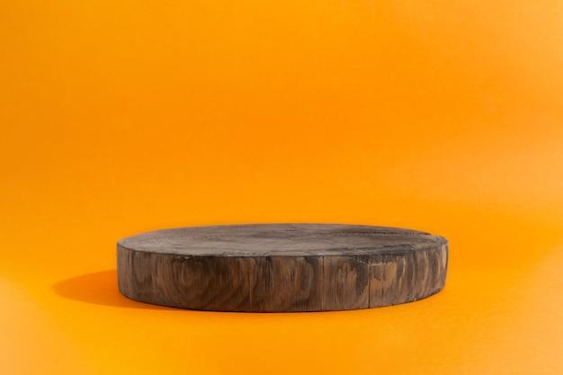 Vitrine vide de podium de cercle en bois sur l'affichage de vitrine de fond orange