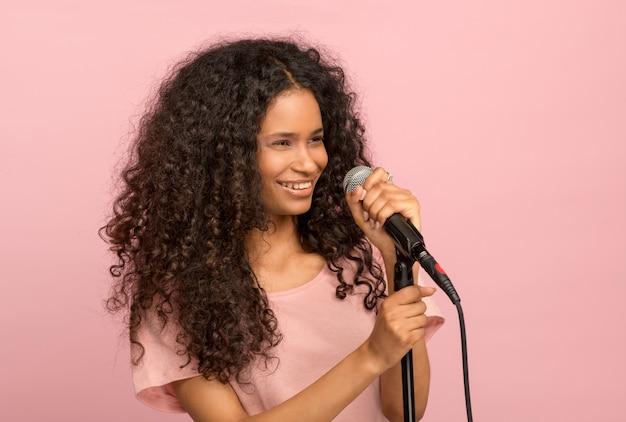 Vivace jeune fille noire avec un microphone