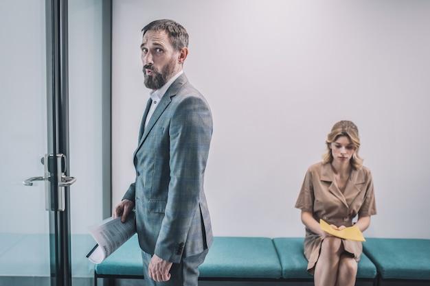Vivre. inquiet homme triste en costume gris d'affaires avec des documentaires entrant dans le bureau et jeune femme en attente dans le couloir