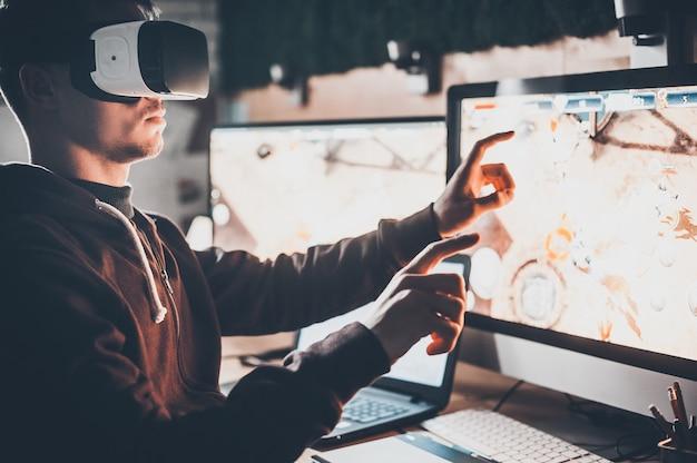 Vivre la réalité virtuelle. beau jeune homme portant un casque de réalité virtuelle et gesticulant assis à son bureau dans un bureau créatif