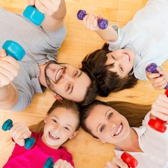 Vivre une vie active. vue de dessus d'une famille sportive heureuse se liant les uns aux autres en position allongée sur le sol et en tenant des haltères