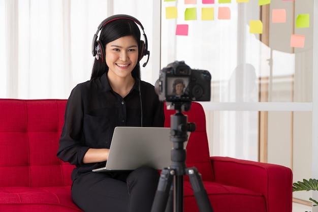 Vlog femme asiatique blogueuse influenceur assis sur le canapé à la maison et enregistrement vidéo blog