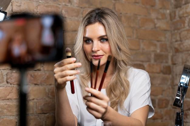 Vlogger de beauté faisant une vidéo avec des cosmétiques