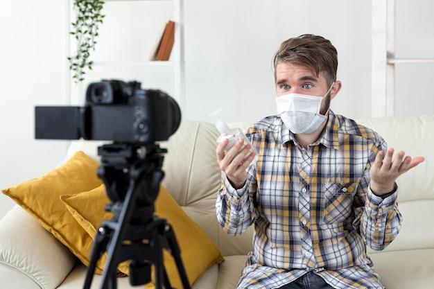 Vlogger enregistrant une vidéo à la maison avec un désinfectant pour les mains