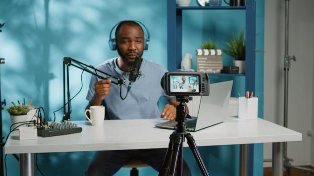 Vlogger enregistrant une vidéo pour un podcast en ligne et regardant un ordinateur portable