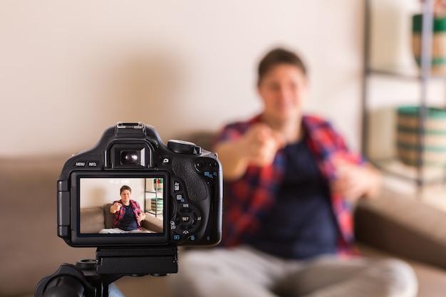 Un vlogger enregistre une vidéo sur les réseaux sociaux assis sur le canapé