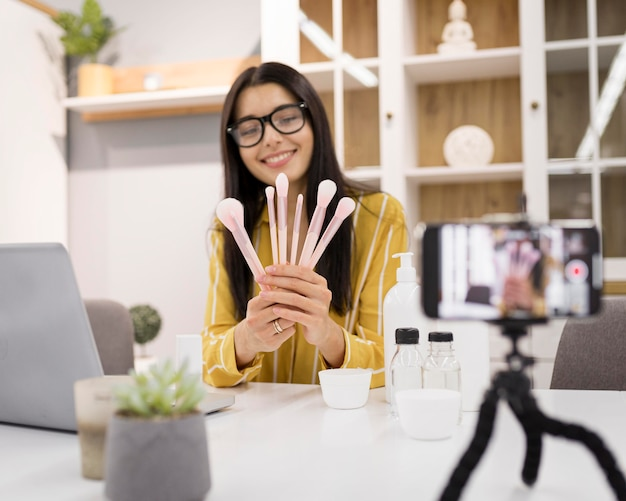 Vlogger femelle à la maison avec ordinateur portable et pinceaux