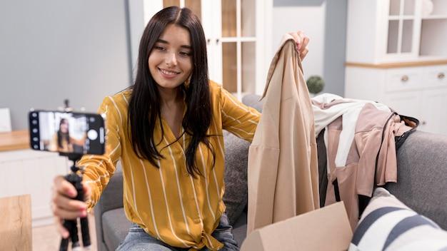 Vlogger femelle à la maison avec des vêtements de déballage de smartphone