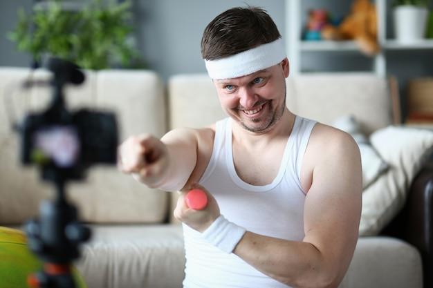 Vlogger heureux avec la formation d'haltères en appartement. sportif souriant, enregistrement vidéo sur caméscope numérique pour vlog sport.