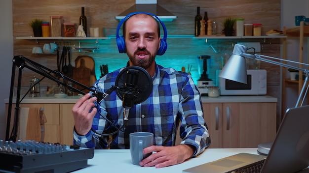 Vlogger regardant la caméra tout en parlant dans le microphone pendant le podcast de divertissement. émission créative en ligne production en direct hôte de diffusion sur internet diffusant du contenu en direct, enregistrement numérique social moi