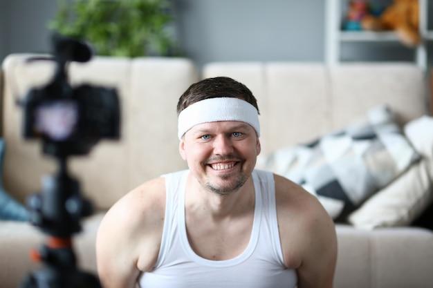 Vlogger souriant, enregistrement d'une vidéo de remise en forme sur l'appareil photo. happy bearded man shooting video for sport vlog in apartment. guy pratique un mode de vie sain.