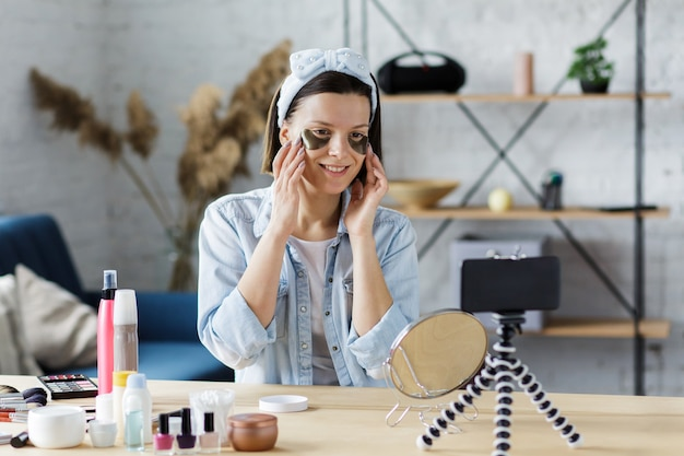Vlogger teste des coussinets oculaires et diffuse une vidéo en direct sur le réseau social à la maison