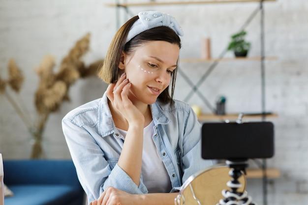 Vlogger teste la crème pour le visage et diffuse une vidéo en direct sur le réseau social à la maison.