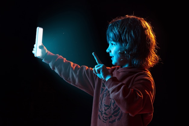 Vlogging avec smartphone. portrait de garçon caucasien sur fond sombre de studio en néon. beau modèle aux cheveux bouclés. concept d'émotions humaines, expression faciale, ventes, publicité, technologie moderne, gadgets.