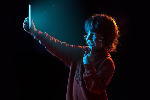 Vlogging avec smartphone. portrait de garçon caucasien sur un mur sombre en néon. beau modèle aux cheveux bouclés. concept d'émotions humaines, expression faciale, ventes, publicité, technologie moderne, gadgets.