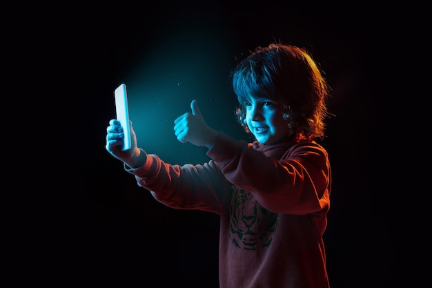 Vlogging avec smartphone, pouce vers le haut. portrait de garçon caucasien sur fond sombre en néon. beau modèle bouclé. concept d'émotions humaines, expression faciale, ventes, publicité, technologie moderne, gadgets.