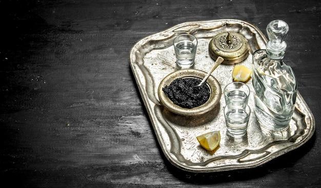 Vodka au caviar sur l'ancien plateau. sur un tableau noir.