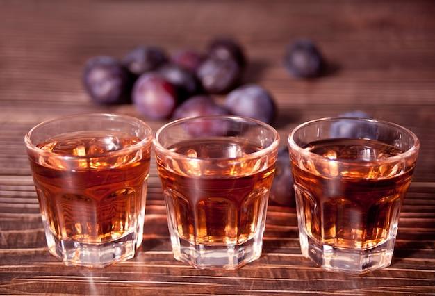 Vodka aux prunes ou brandy aux prunes fraîches sur table en bois.