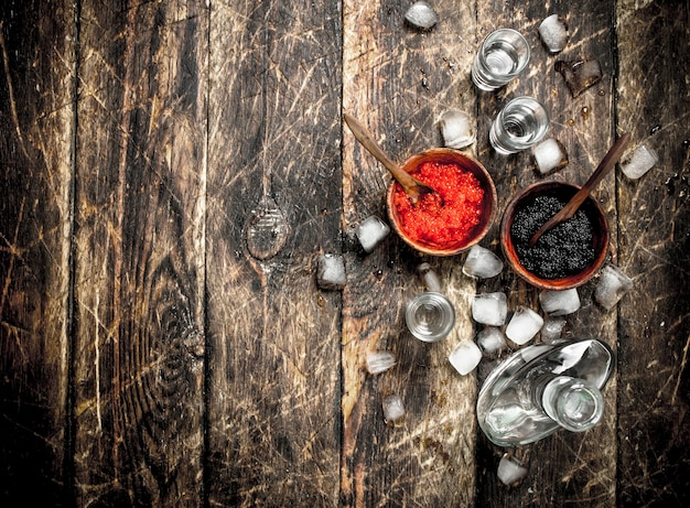 Vodka en bouteille avec du caviar noir et rouge. sur fond de bois.