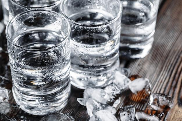 Vodka dans des verres à liqueur sur bois rustique