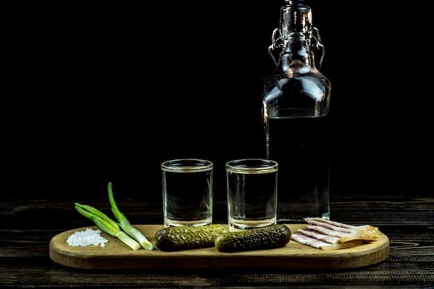 Vodka et deux verres et concombres avec bacon et oignons