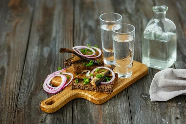 Vodka avec du poisson et du pain grillé sur table en bois