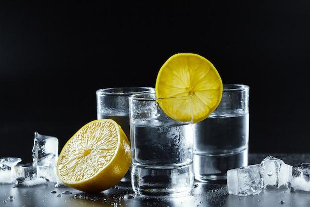 Vodka froide dans des verres sur un fond noir.