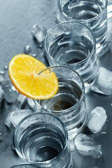 Vodka froide dans des verres à liqueur sur fond noir.