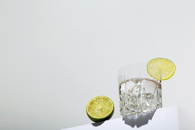 Vodka avec glace et citron vert en verre sur support blanc. vue de héros, ombres et tendances de la lumière du soleil. copier l'espace