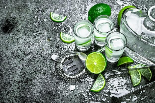 Vodka avec des morceaux de citron vert et des glaçons sur une table rustique