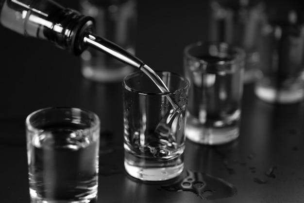 Vodka, rhum, tequila, gin sont versés dans des verres au bar.