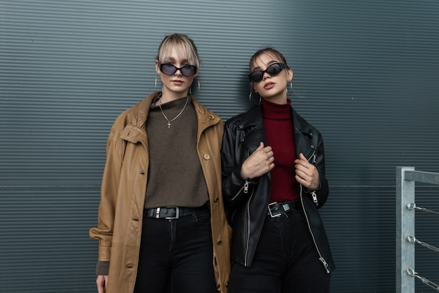Vogue deux jeunes femmes à la mode dans des lunettes de soleil élégantes dans des vestes en cuir avec un jean noir posant près d'un mur de métal dans la rue